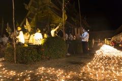 Stearinljusljus som betalar respekt till den buddha reliken på den buddistiska templet Arkivbild