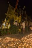 Stearinljusljus som betalar respekt till den buddha reliken på den buddistiska templet Arkivfoto
