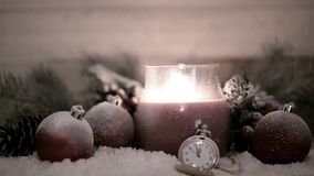 Stearinljuslykta, julbollar och klocka arkivfilmer