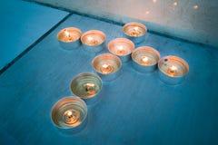 Stearinljusteljus i kristet kors korsar bildande Fotografering för Bildbyråer