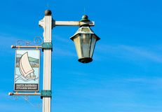 Stearn`s Wharf welcome banner with carriage lamp on metal pole. Stearn`s Wharf welcome banner with a vintage carriage lamp on a metal street pole in Santa Royalty Free Stock Photo