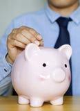 Stecken eines Geldes in eine piggy Querneigung Stockbild