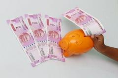 Stecken eines Geldes in eine piggy Querneigung stockbilder