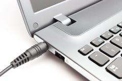 Steckeradapter, der an Laptop-Computer angeschlossen wird Stockfoto