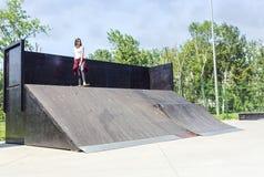 Stedelijk skateboardermeisje die bij de helling van het vleetpark met een skateboard rijden stock fotografie