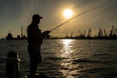 Stedelijk visserijconcept Silhouet van visser op de industriële achtergrond van de zeehavenstad stock fotografie