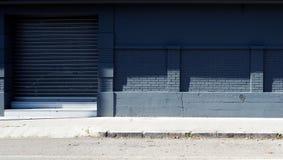 Stedelijke Achtergrond Grijze baksteen en concrete muur met een blind aan de kanten van de straat royalty-vrije stock foto
