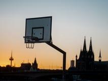 Stedelijke Basketbalhoepel met horizon van Keulen, Duitsland, in backg stock fotografie