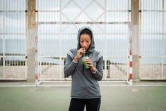 Stedelijke geschiktheidsvrouw die detox smoothie op trainingrust drinken stock foto