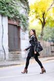 Stedelijke jonge vrouw die in de stad van het leerjasje lopen stock afbeeldingen