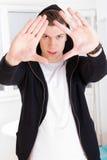 Stedelijke in kerel die kap dragen die zijn gezicht met handen ontwerpen Stock Fotografie