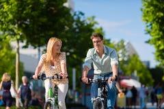 Stedelijke paar berijdende fiets in vrije tijd stock foto