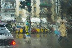 Stedelijke scène door nat venster stock fotografie