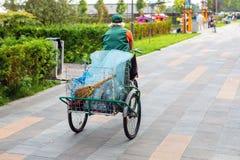 Stedelijke straat schonere berijdende fiets met vuilniszak door gemeentelijk park op zonnige dag Vegerarbeider met fiets op bestr stock foto
