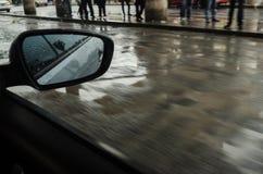 Stedelijke straat van binnenuit een bewegende auto, regenachtige dag in een stad, mensen op de stoep op een regenachtige dag stock foto's