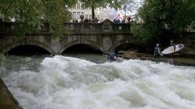 Stedelijke Surfers op een kunstmatige golf op de Eisbach-rivier in het centrum van München, Duitsland stock videobeelden
