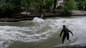 Stedelijke Surfers op een kunstmatige golf op de Eisbach-rivier in het centrum van München Langzame Motie stock video