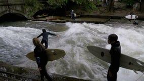 Stedelijke Surfers op een kunstmatige golf op de Eisbach-rivier in het centrum van München Langzame Motie stock footage
