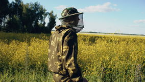 Stedicam shot of beekeeper walking and inspecting blossoming field of flowers near apiary stock footage