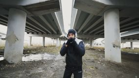 Stedicam shot of boxer man in headphones doing boxing exercise while listen music in urban location outdoors in winter stock footage