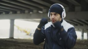 Stedicam shot of sportive man boxer in headphones doing boxing exercise in urban location outdoors in winter stock footage
