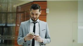 Stedicam tiró de hombre de negocios alegre usando smartphone y caminar en pasillo moderno de la oficina