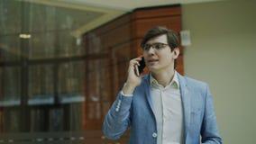 Stedicam tiró del hombre de negocios alegre que hablaba con smartphone y que caminaba en pasillo moderno de la oficina
