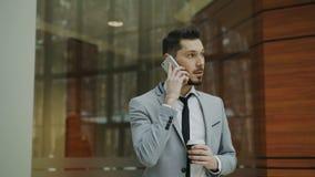Stedicam tiró del hombre de negocios que hablaba con smartphone y que caminaba en pasillo moderno de la oficina