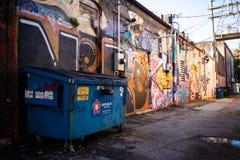 Steegmanier met graffiti en een dumpster royalty-vrije stock foto's