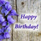 Steekt de kaart` Gelukkige verjaardag `, houten achtergrond, violette bloemen van aan viooltjes royalty-vrije stock afbeelding