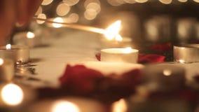 Steekt een kaars, aangestoken kaarsen aan, nam bloemblaadjes, het defocusing toe stock videobeelden