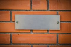 Steel or aluminum company name plate. With brick wall background or building name plate royalty free stock images