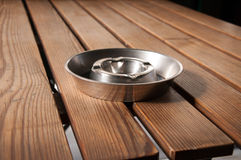 Steel ashtray. On a wood table Royalty Free Stock Image