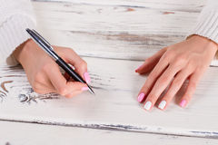 Steel ball pen in female hand. Royalty Free Stock Images