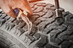 Steel bar puncture car tire. With technician service Stock Photo