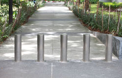 Steel barrier on the sidewalk in the park. Royalty Free Stock Photo