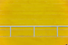 Steel barriers. Yellow stadium bleachers with white steel guard rail for sport background royalty free stock photo