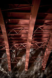 Steel Beam Bridge Reflections. Red steel beams underneath a bridge with reflections Royalty Free Stock Photography