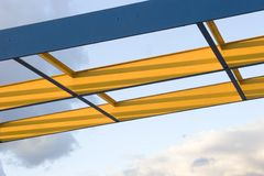 Steel Beams. Blue and yellow steel beams against a cloudy sky stock images