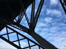 Steel beams under bridge structure. Steel beams under a bridge in Pennsylvania with blue sky and clouds gray steal structure royalty free stock photo