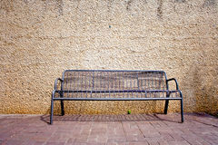 Steel bench by the wall. Black steel bench by the concrete wall Stock Images