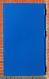 Steel blue door brick house Stock Photo