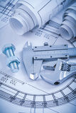 Steel bolt with nut adjustable spanner trammel caliper rolls of. Construction plans on blueprint architecture and building concept Stock Photos