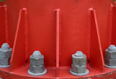 Steel bolt and nuts. On steel plate for fasteners of the bottom of electric pole that red color, selective focus stock photo