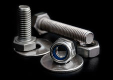 Steel bolts and nuts with washers on black background close-up Stock Image