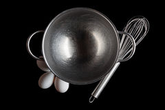 Steel bowl whisker eggs from above on black. Stainless steel bowl with metal whisker and three white eggs aside directly from above on black background royalty free stock photos