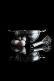 Steel bowl whisker eggs side view with reflection vertical black. Stainless steel bowl with metal whisker and three white eggs aside side view with reflection on royalty free stock image