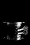 Steel bowl with whisker from side with reflection vertical. Stainless steel bowl with metal whisker aside on black background from side with reflection vertical stock photo