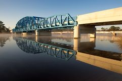 Steel Bridge. Blue steel bridge over the St Marys River with its reflection in the water Stock Images