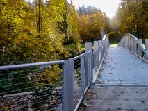 Steel bridge extending to fall park. Shiny metal bridge leading over river to brightly lit autumn park Royalty Free Stock Photo